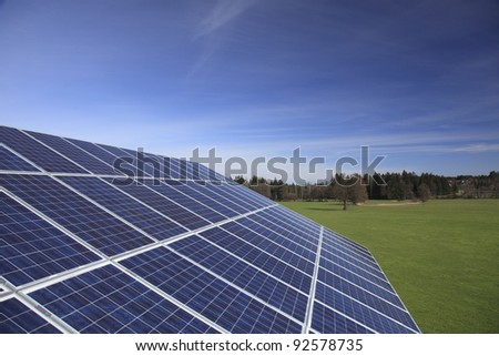 Photovoltaic panels on roof top with field in background - stock photo