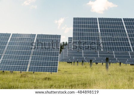Photovoltaic panels power plant on meadow against cloudy sky - Ecology energy source