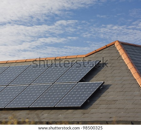 Photovoltaic Solar panels Mounted on a slate roof of residential or private home - stock photo