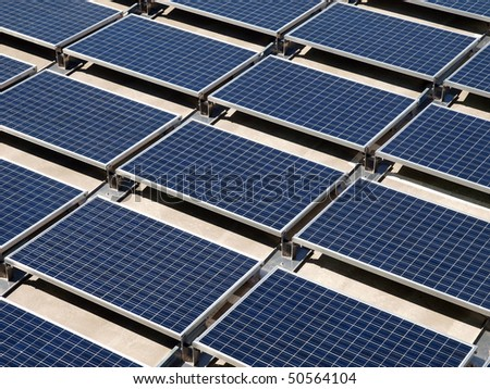 Photovoltaic solar panels on a concrete rooftop. - stock photo