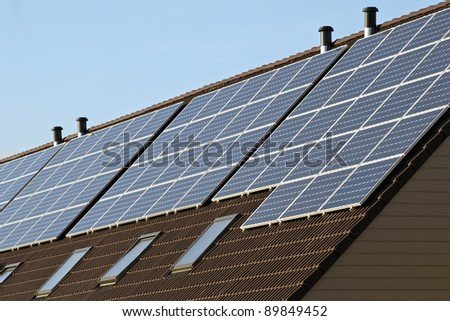Photovoltaic solar panels on several houses - stock photo