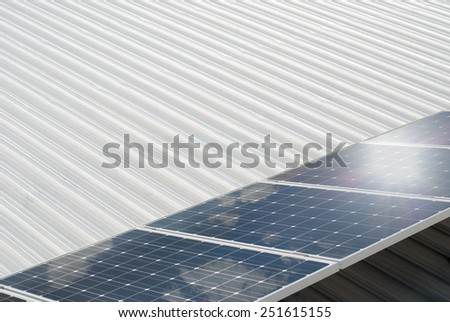 Photovoltaic system installed on a metal industrial roof - stock photo