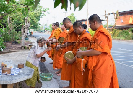 PHRAE - THAILAND , MAY 1 - 2016 : Row of Thai Buddhist young adult monk walking for food offering in morning , thai culture and religion in THAILAND.