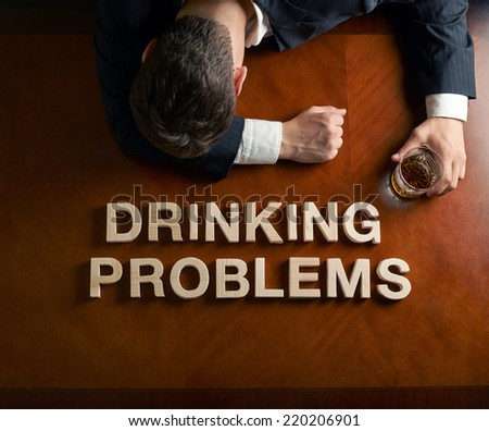 Phrase Drinking Problems made of wooden block letters and devastated caucasian man in a black suit sitting at the table with the glass of whiskey, top view composition with dramatic lighting - stock photo
