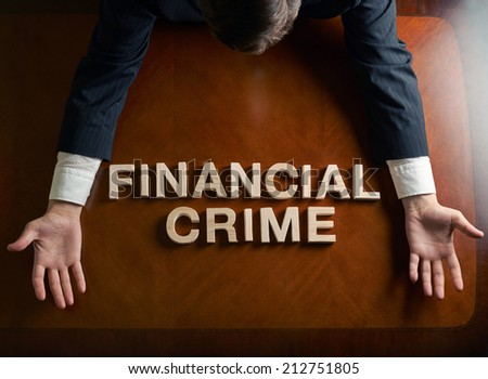 Phrase Financial Crime made of wooden block letters and devastated middle aged caucasian man in a black suit sitting at the table, top view composition with dramatic lighting - stock photo