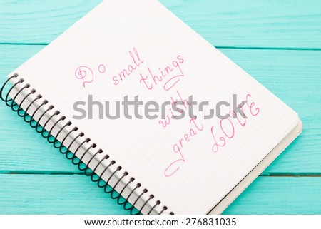 Phrase in notebook - do small things with great love on blue wooden background. Top view. Selective focus. Macro - stock photo
