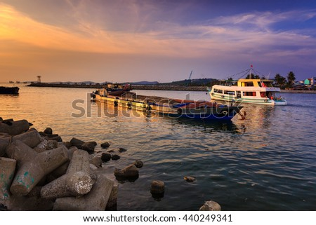 Phu Quoc island, Kien Giang province, Vietnam - May 02, 2016: amazing sunset at breakwater pier on Phu Quoc island . scene the boats were operating on the river to prepare to the sea in the sunset