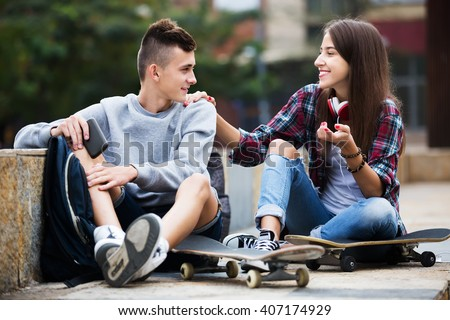 Phubbing: teenager boy and girl asking for attention in the city. Focus on boy - stock photo
