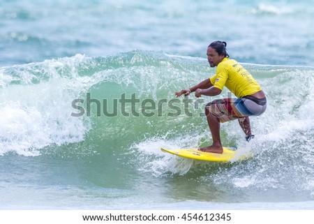 PHUKET - JULY 17: unidentified surfer in action catching waves in rainy season at Kata beach Phuket on July 17, 2016 in Kata beach, Phuket, Thailand. - stock photo