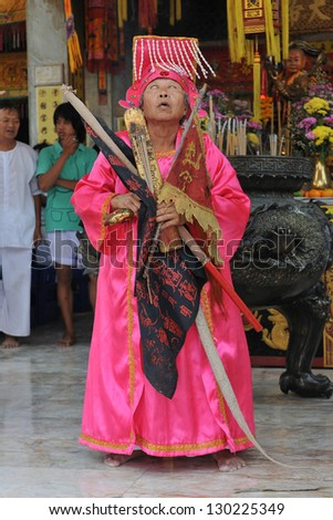 PHUKET - OCT 2: A Taoist devotee participates in a ceremony of the Nine Emperor Gods Festival, known locally as the Phuket Vegetarian Festival, at a Chinese temple on Oct 2, 2011 in Phuket, Thailand. - stock photo