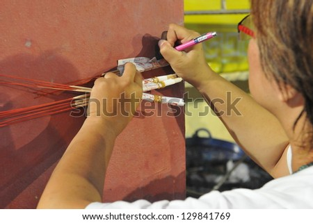 PHUKET - OCT 5: A temple-goer writes wishes on paper during a ceremony of the Nine Emperor Gods Festival, known locally as the Phuket Vegetarian Festival, on Oct 5, 2011 in Phuket, Thailand. - stock photo