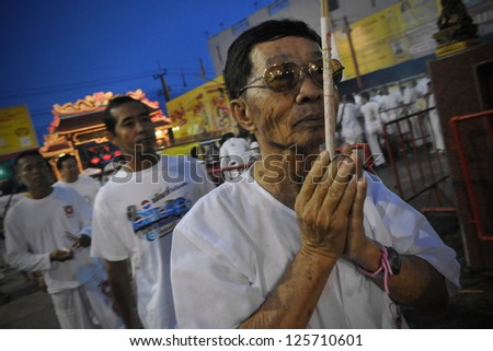 PHUKET - OCT 4: An unidentified man prays at a Taoist shrine during the Nine Emperor Gods Festival, known locally as the Phuket Vegetarian Festival, on Oct 4, 2011 in Phuket, Thailand.