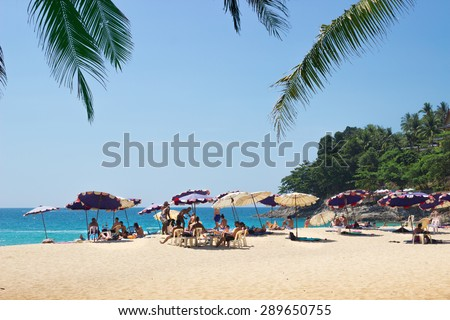 PHUKET, THAILAND - CIRCA MAR 2015: People relax on the sandy beach in February 2015 in Phuket. Despite the holiday season, there is still not very crowded places in Phuket - stock photo