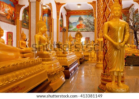 PHUKET, THAILAND - FEB 6: Crowd of golden Buddha statues in different poses inside Wat Chalong temple on February 6, 2016. First written mention about the buddhist monastery belongs to 1837 - stock photo