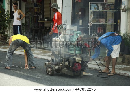 PHUKET, THAILAND - JUNE 9 : Thai man working mark line thermoplastic traffic routes on the road at soi rommanee on thalang road on June 9, 2016 in Phuket, Thailand