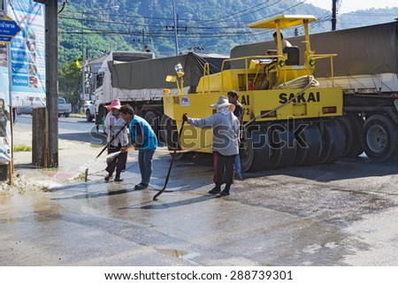 PHUKET, THAILAND - MAR 03, 2015: People are working on repairing the road surface in the Thai village - stock photo