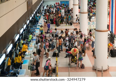 PHUKET, THAILAND - 06 MAY 2014: Passengers registering on check-in desks the international departures area at Phuket International Airport. - stock photo