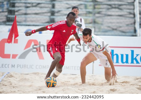 PHUKET THAILAND-NOVEMBER20 :Hasan Alhammadi (red) of UAE in action during the Beach Soccer match between UAE and Iran the 2014 Asian Beach Games at Saphan Hin on Nov 20,2014 in Thailand - stock photo