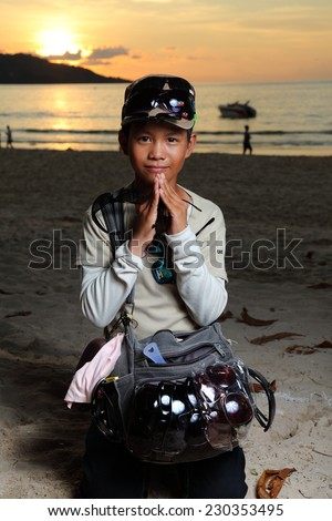PHUKET, THAILAND - OCTOBER 29, 2014: A photo of a young Thai boy selling sunglasses to tourist at Patong Beach, Phuket, Thailand.