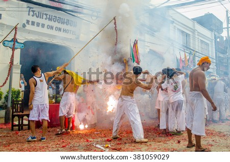 PHUKET, THAILAND - OCTOBER 17, 2015: Firecrackers exploding over devotees responsible for carrying the sedan chairs with the god's image at the Vegetarian Festival.