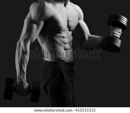 Physical condition on peak. Monochrome cropped shot of a male bodybuilder posing shirtless showing off his sexy abs holding dumbbells  - stock photo