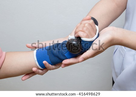 Physical therapist assisting patiant woman in lifting dumbbells,rehabilitation concept - stock photo