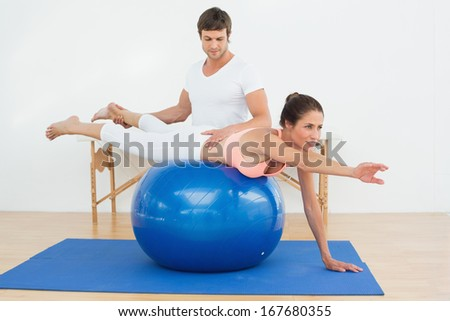 Physical therapist assisting young woman with yoga ball in the gym at hospital - stock photo