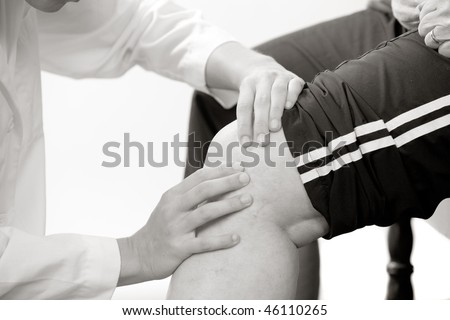 physical therapist checks a knee joint - stock photo