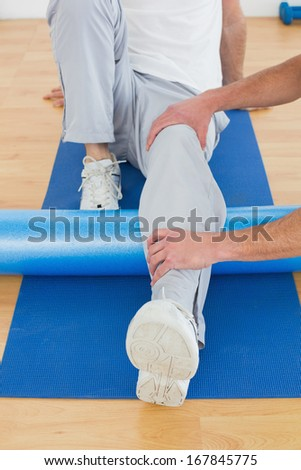 Physical therapist examining young man's leg at the hospital gym - stock photo