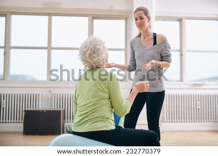 Physical therapist explaining health benefits to a senior woman at gym. Female trainer discussing progress with elderly woman at health club. - stock photo
