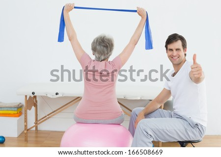 Physical therapist gesturing thumbs up besides senior woman on yoga ball - stock photo