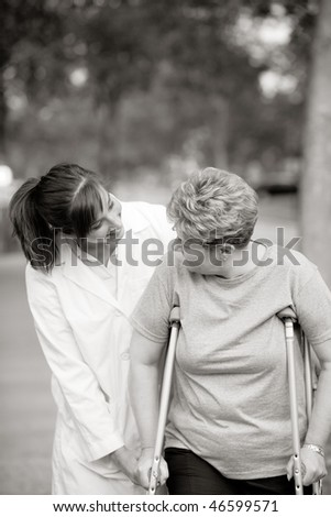 physical therapist helping a woman on crutches