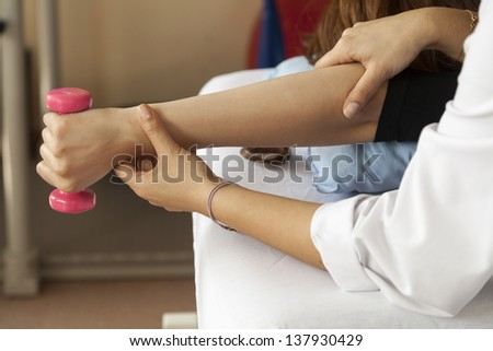Physical therapist helps a patient at a physiotherapy session - stock photo