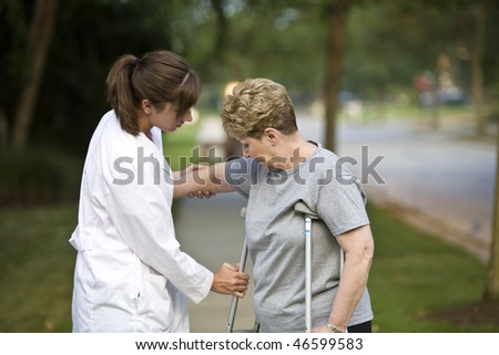 Physical therapist helps a patient with crutches - stock photo