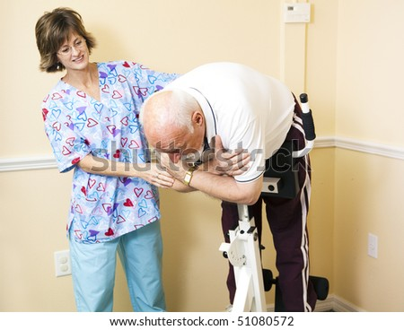 Physical therapist in a chiropractors office helping a patient to stretch his spine on a Roman Chair. - stock photo