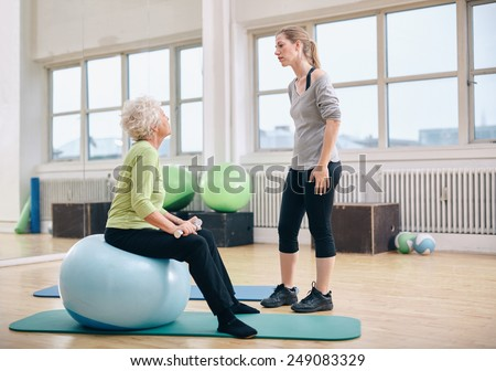 Physical therapist instructing a senior woman at rehab. Female trainer talking with old woman sitting on fitness ball holding dumbbells at gym.