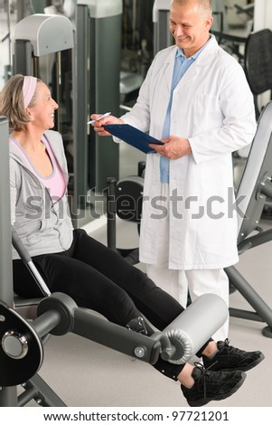Physical therapist male assist active senior woman exercise at gym - stock photo