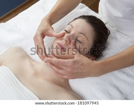 physical therapist practicing a facial massage - stock photo