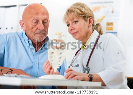 Physical therapist talking to patient and explains the cause of his pain - stock photo