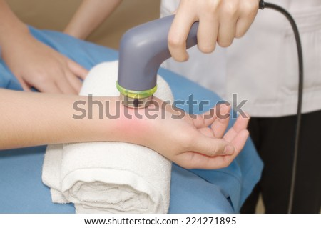 Physical therapist using ultrasound probe on woman patient 's hand for release pain - stock photo