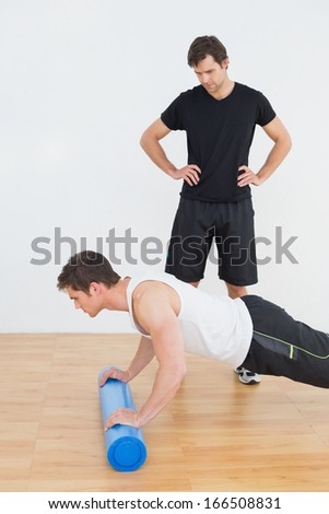 Physical therapist watching young man do push ups in the gym at hospital