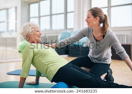 Physical therapist working with a senior woman at rehab. Female trainer helping senior woman doing exercise on foam roller at gym. - stock photo