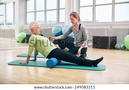 Physical therapist working with active senior woman at rehab.  Old woman exercising using foam roller with personal trainer at gym. - stock photo