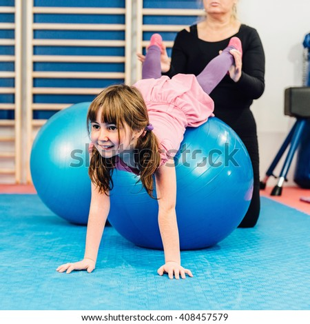 Physical therapist working with little girl in gym, exercising with fitness ball - stock photo