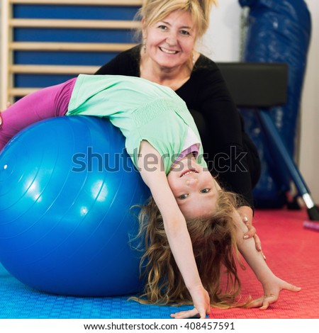 Physical therapist working with little girl in school gymnasium, exercising with fitness ball - stock photo