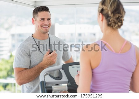 Physical trainer helping woman on treadmill at gym - stock photo