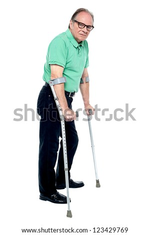 Physically disabled old man walking with the help of crutches, looking depressed - stock photo