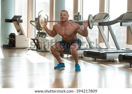 Physically Fit Man Exercising Legs By Doing Squats - stock photo