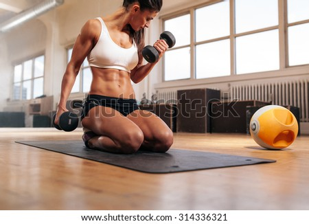 Physically fit woman at the gym lifting dumbbells to strengthen her arms and biceps. Muscular woman sitting on exercise mat looking at her arms. - stock photo