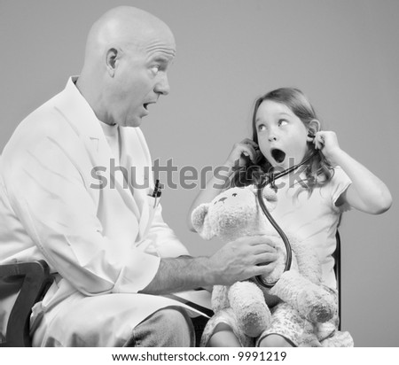 Physician Examining Girl and Her Bear - stock photo